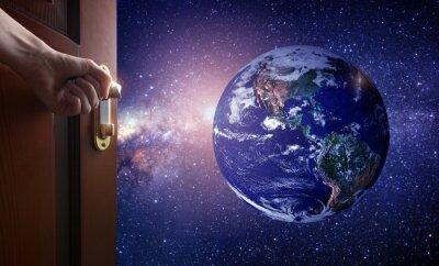Фотообои Рука открывает пустую дверь комнаты на планету Земля из космоса. Некоторые