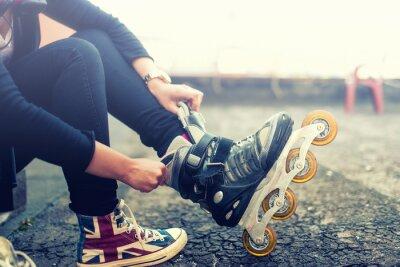 Фотообои Молодая девушка, наслаждаясь катание на роликах, роликовых коньках, положив на роликовых коньках после деятельности. Урожай эффект на фото