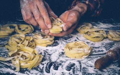 Фотообои Homemade uncooked pasta on black background. Making fresh italian fettuccine.