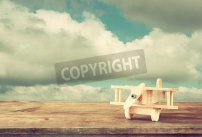 Фотообои Изображение деревянный игрушечный самолет над деревянным столом против облачного неба. Изображение в стиле ретро