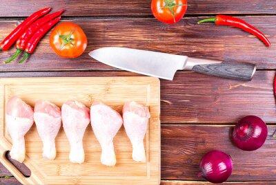Нож, куриные ноги и овощи на старом столе: помидоры, огурцы, перец, лук, листья салата