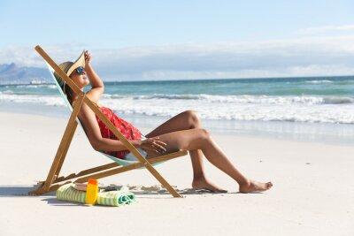 Фотообои Mixed race woman on beach holiday sitting in deckchair sunbathing