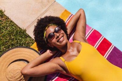 Фотообои Mixed race woman sunbathing by pool on a sunny day smiling