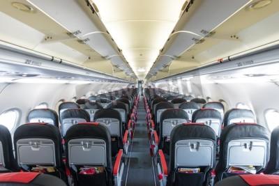 Фотообои Modern interior of aircraft. Black and red seats inside airplane. Symmetric vanishing row of seats inside air transport. Economy class of flight. Equipment for travelling. Empty illuminated plane.