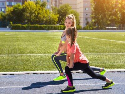 Фотообои Мать и маленькая дочь делают упражнения на стадионе. Он
