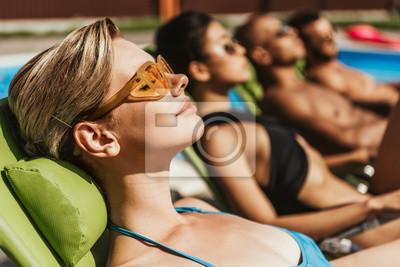 Фотообои многонациональные друзья в солнечных очках, загорая на шезлонгах у бассейна, выборочный фокус