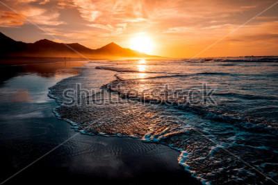 Фотообои Удивительный пляжный закат с бесконечным горизонтом и одинокими фигурами на расстоянии, и невероятными пенистыми волнами. Вулканические холмы на заднем плане в идиллических теплых тонах.