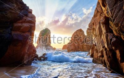 Фотообои Песчаный пляж среди скал на вечернем закате. Пляж Ursa около мыса Рока (Cabo da Roca) на побережье Атлантического океана в Португалии. Летний пейзаж