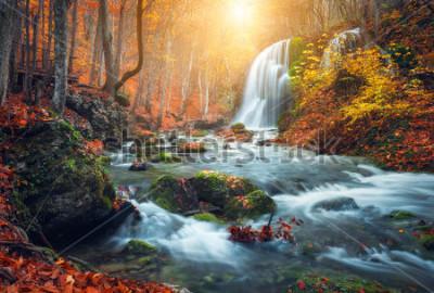 Фотообои Красивый водопад на горной реке в красочный осенний лес с красными и оранжевыми листьями на закате. Природный ландшафт