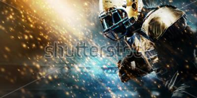 Фотообои American football sportsman player on stadium running in action. Sport wallpaper with copyspace.
