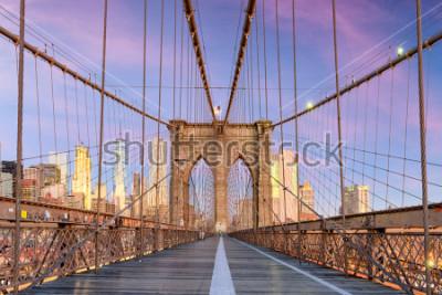 Фотообои New York, New York on the Brooklyn Bridge Promenade facing Manhattan's skyline at dawn.
