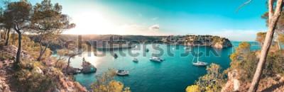 Фотообои Панорамный вид на пляж залив с бирюзовой водой и парусных лодок и яхт на якоре с рамкой сосны. Прекрасный романтический Cala Portals Vells, Майорка, Испания. Балеарские острова
