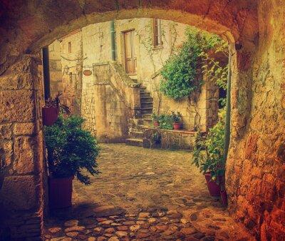 Фотообои Узкие улицы средневекового города Sorano туф с арочными, зеленые растения и булыжник, путешествия Италия старинные фон