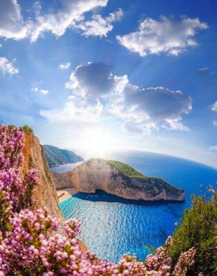 Фотообои пляж Навагио с кораблекрушения и цветы на фоне заката солнца, остров Закинф, Греция
