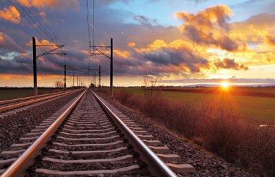 Фотообои Оранжевый закат в низких облаках над железной дорогой