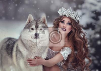 Фотообои Портрет женщины в серебряном платье и короне, как снежная королева, в зимнем лесу с хаски. Фея Принцесса и волк зимой.