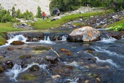 Фотообои Быстрое и широкое каскад реки Быстрое перемещение воды яркие скалистые камни и группы людей, идущих на зеленый луг на фоне