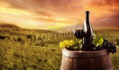 Фотообои Красная бутылка вина и стекла на деревянной бочке. Виноградник на фоне