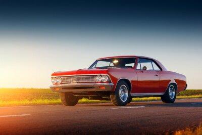 Фотообои Ретро красный автомобиль пребывание на асфальтированной дороге на закате