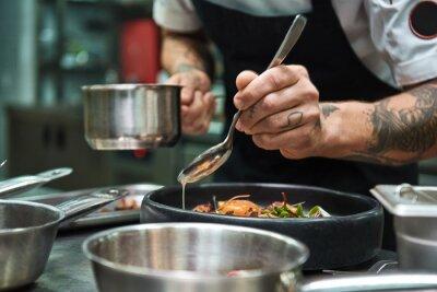 Фотообои Secret recipe. Close up photo of chef hands with several tattoos adding a sauce to italian pasta Carbonara.
