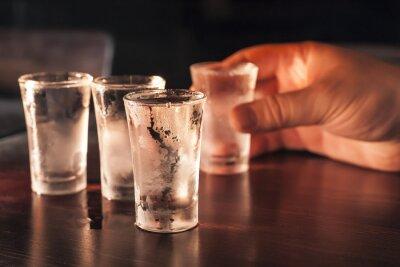 Фотообои Выстрел стакан водки в руке на деревянный стол.