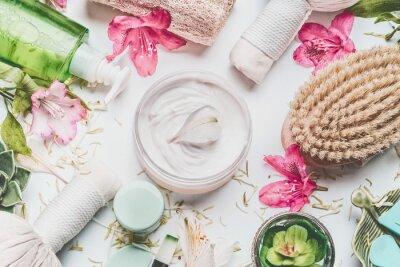 Фотообои Крем для кожи с цветами лепестки и другие средства по уходу за телом косметические продукты и аксессуары на белом фоне, вид сверху