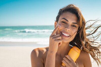 Фотообои Smiling woman applying sunscreen
