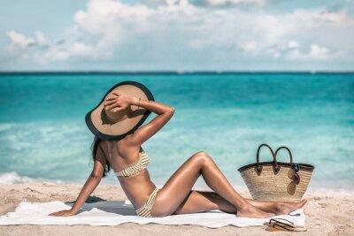 Фотообои Suntan summer holiday bikini woman tanning relaxing on beach. Retro fashion lady wearing straw hat sunbathing under the Caribbean sun vacation.