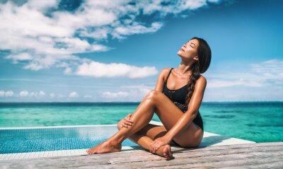 Фотообои Swimsuit model beauty skincare suntan Asian woman posing sunbathing tanning in black one piece bathing suit. Beautiful girl relaxing at overwater infinity pool luxury resort. Spa, wellness, laser.