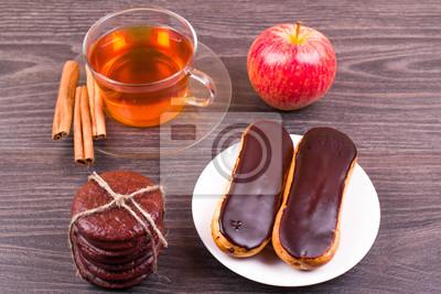 Чай, эклеры и корицу на столе