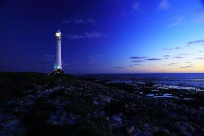 Фотообои На маяк / с видом вечернего маяка Slangkop с камнями и облаками