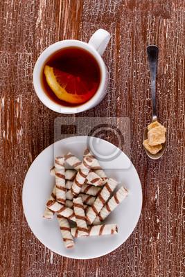 Трубочки вафельные и чай с лимоном на старом столе