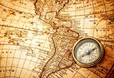 Фотообои Vintage compass lies on an ancient world map.