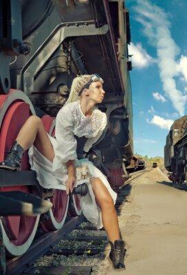 Фотообои Женщина в винтажном платье сидит на колесе локомотива.