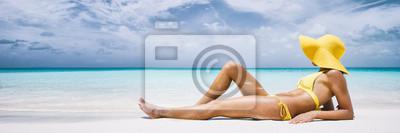 Фотообои Woman on beach vacation lying down with beach hat sunbathing by turquoise water