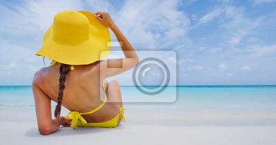 Фотообои Женщина на пляжном отдыхе лежа в песке с шляпой пляжа загорая совершенным бирюзовым океаном. Элегантный молодой взрослый на женщину для тропического путешествия роскошных праздников.