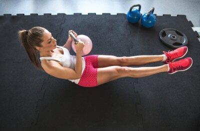 Фотообои Woman working on her abs with kettlebell