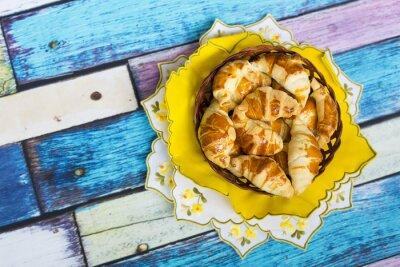 Фотообои Самодельные круассаны в плетеной корзинке на желтой салфетке с цветочным узором на старом / вытертом полу
