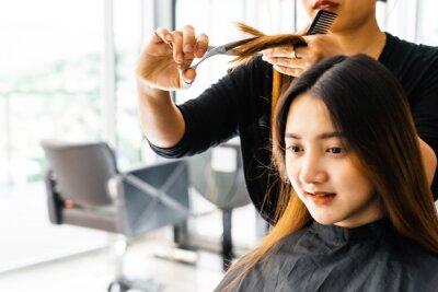 https://img.myloview.ru/murals/young-asian-beautiful-woman-having-her-hair-cut-at-the-hairdresser-s-scissors-cut-the-girls-hair-barber-student-cutting-hair-using-puppet-400-214255494.jpg