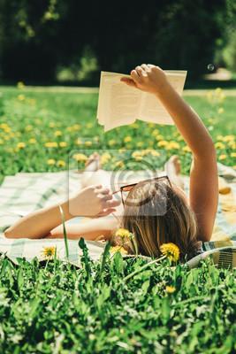 Фотообои Молодая женщина лежа на одеяле в домашнем дворе и загорая на солнечный день и читая реальную книгу. Трава и dandilion фон, красивый винтажный вид.