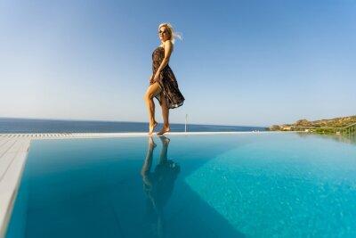 Фотообои Young woman sunbathing near swimming pool.
