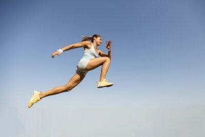 Фотообои Молодая женщина, принимая прыжок в длину