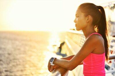 Плакат Активная женщина, отдыхая после работы на круизном судне, глядя на море во время летних каникул. Азиатский бегун девушка носить SmartWatch сердечного ритма монитор активности здорового образа жизни.