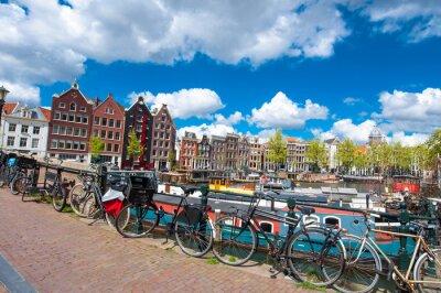 Плакат Амстердам, Нидерланды 27 апреля: Традиционный городской Амстердам с средневекового дома, велосипеды на мосту апреля 27.2015. Амстердам является самым густонаселенным городом Королевства Нидерландов.