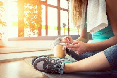 Плакат Привлекательная белокурая женщина с смартфона, отдыхая после тренировки тренажерный зал