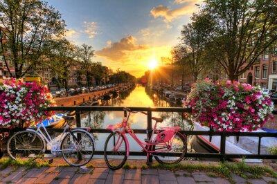 Плакат Красивая восход солнца над Амстердаме, Нидерланды, с цветами и велосипедов на мосту весной