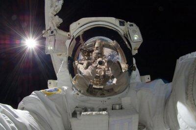 Плакат закрыть вид плавающего астронавта с отражением показа космической станции (некоторые элементы любезно НАСА)