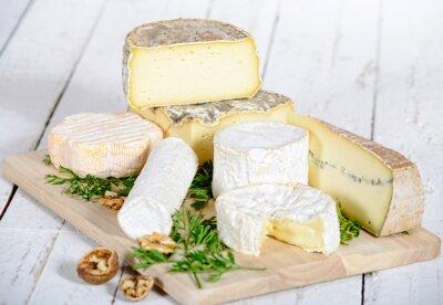 Плакат отличается сыр с грецкими орехами на белом деревянной доске