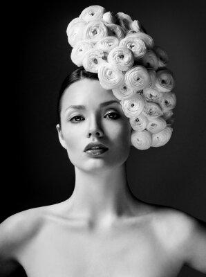 Плакат фотомодель с большой прической и цветы в ее волосы.