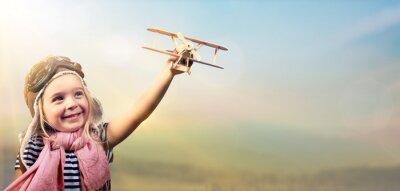 Плакат Свобода мечтать - Радостный ребенок, играющий с самолета на фоне неба